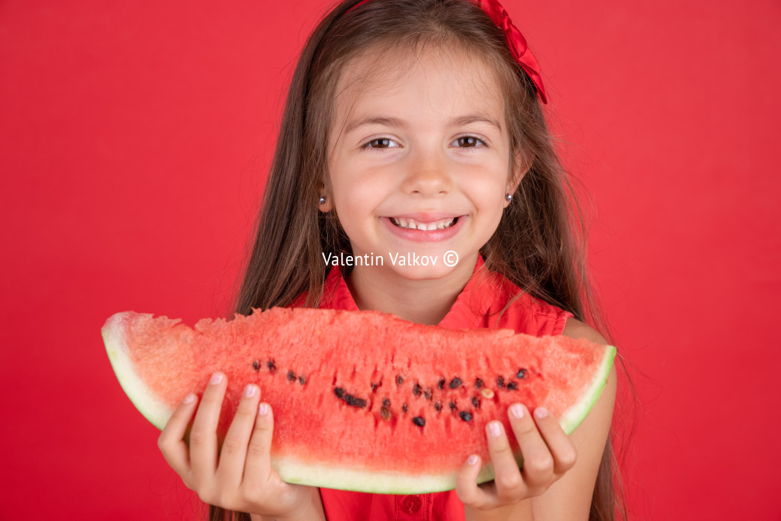 """""""Cute little girl holding, eating juicy slice of watermelon over"""" stock image"""