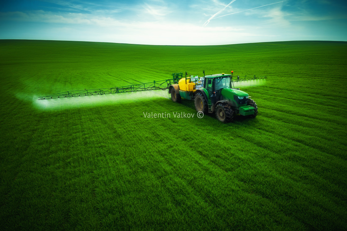 """Aerial view of farming tractor plowing and spraying on field"" stock image"
