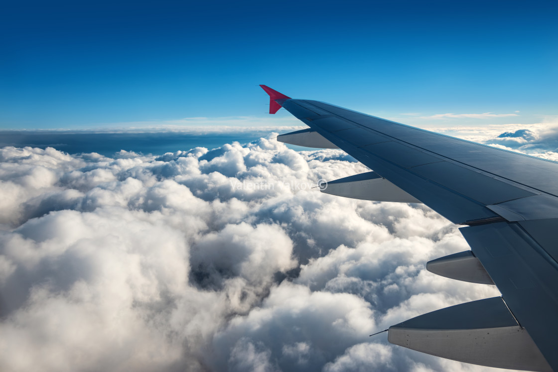 """Wing of an airplane flying above the sky with clouds above the o"" stock image"