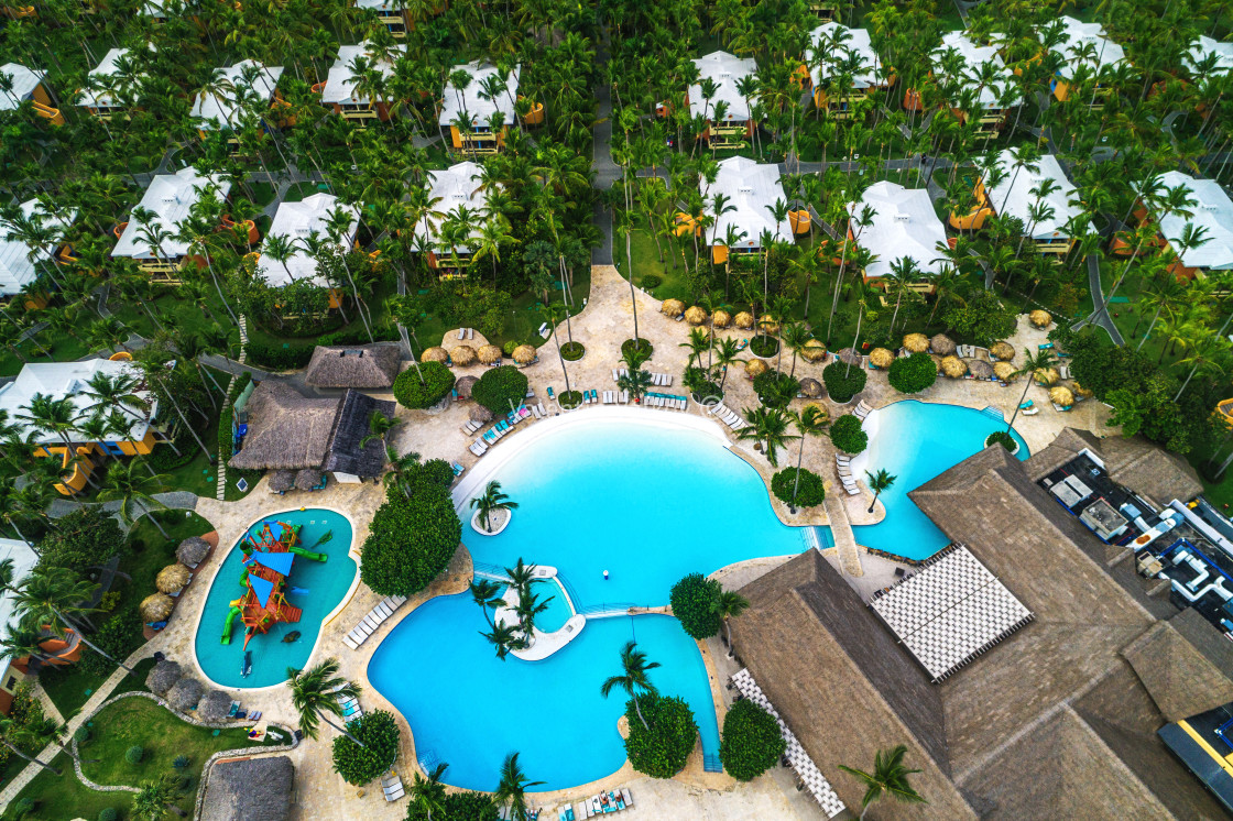 """Aerial view of tropical swimming pool and palm trees in luxury resort"" stock image"