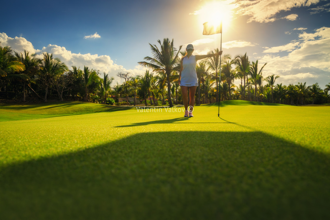 """Young woman golfer standing on tropical golf course, , lens flar"" stock image"