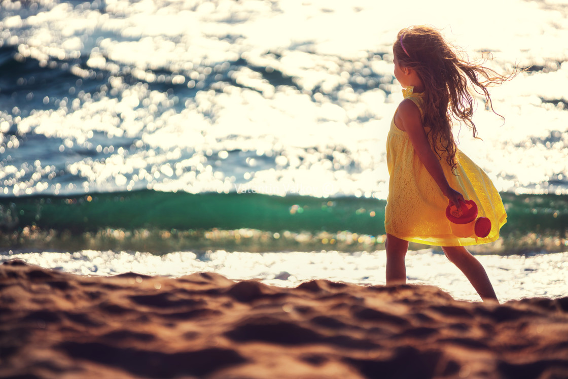 """""""Little girl playing on the beach"""" stock image"""
