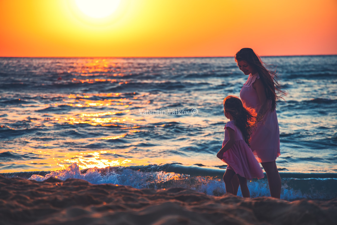 """""""Mother and daughter playing together on the sea beach at sunset"""" stock image"""