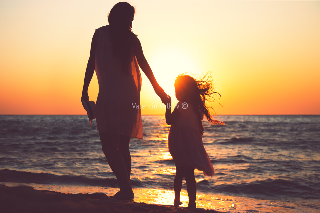 """Mother and daughter playing together on the sea beach at sunset"" stock image"