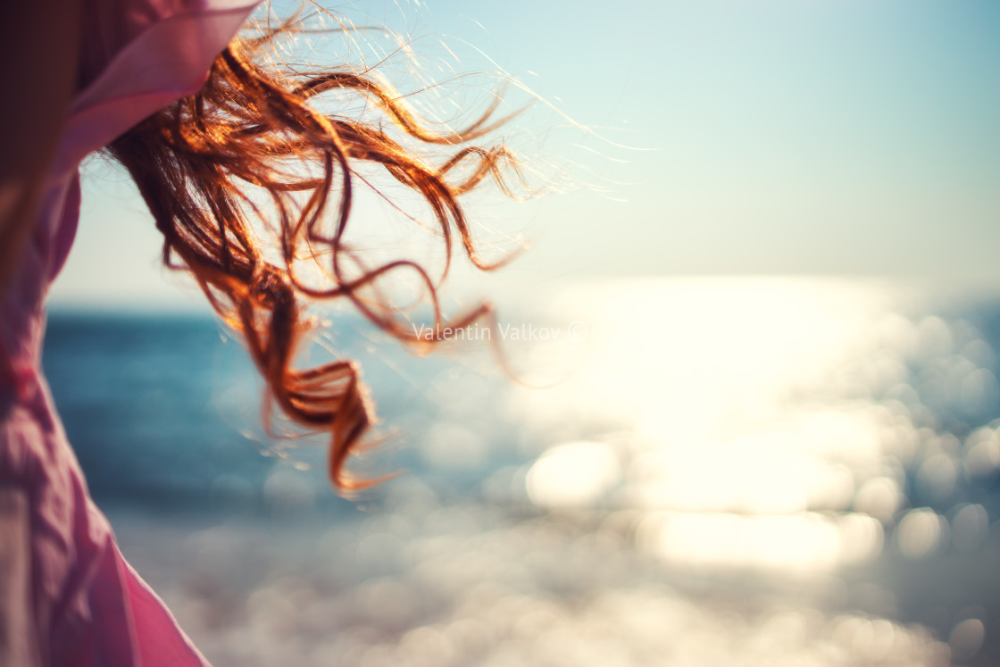 """""""Little girl, kid playing on the beach with wind in her hair"""" stock image"""