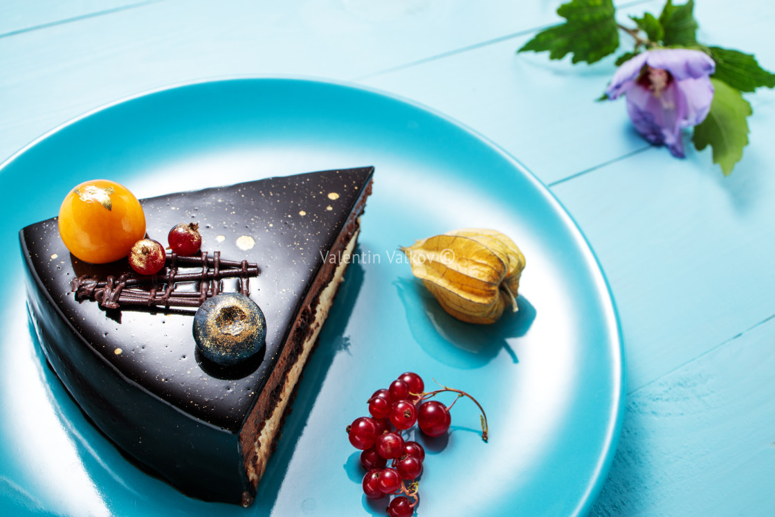 """Chocolate cake with decoration and fruits on blue wooden backgro"" stock image"