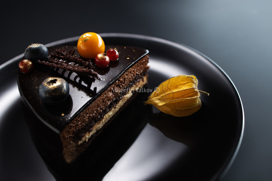 """""""Chocolate cake with decoration and fruits on black background"""" stock image"""