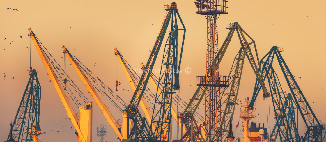 """Sunset over industrial cranes at commercial sea port of the city"" stock image"
