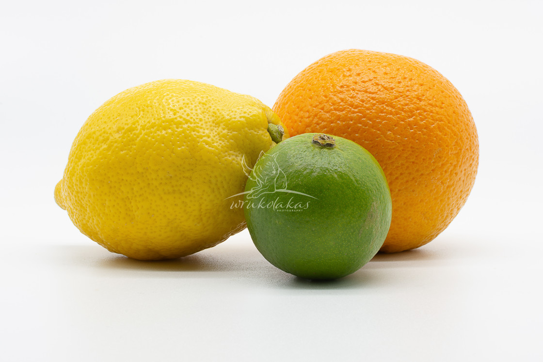 """""""a lime, lemon and orange in the whole in front of white backgrou"""" stock image"""