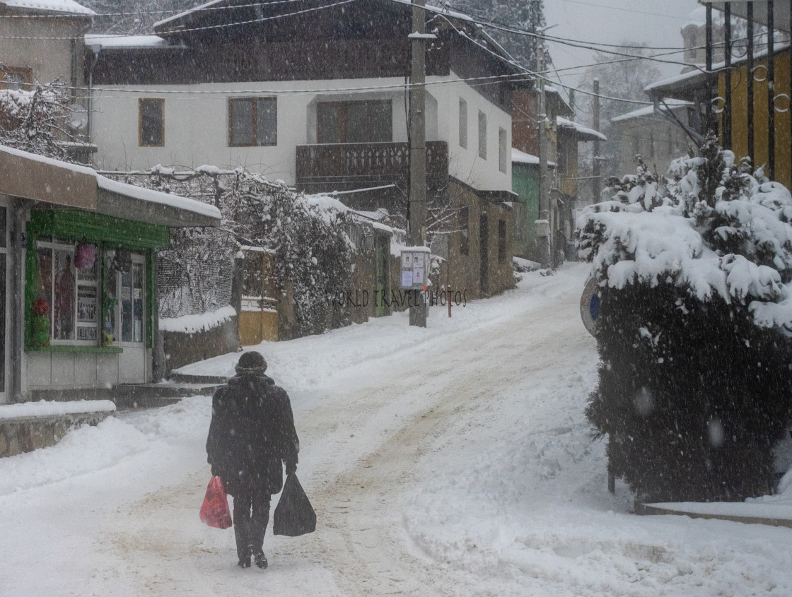 """""""Man Carrying Bags on Snow Covered Street"""" stock image"""