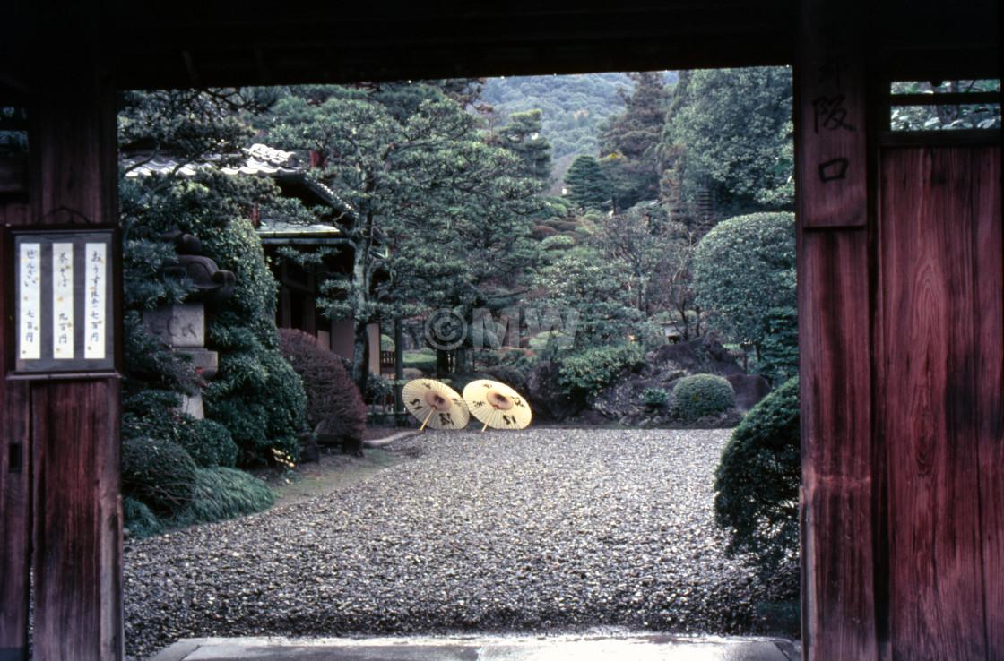 """Two pale yellow parasols seen through Kyoto courtyard gate"" stock image"