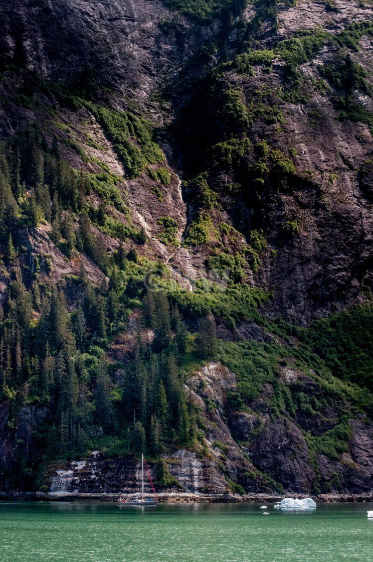 """Yacht dwarfed by mountain wall"" stock image"