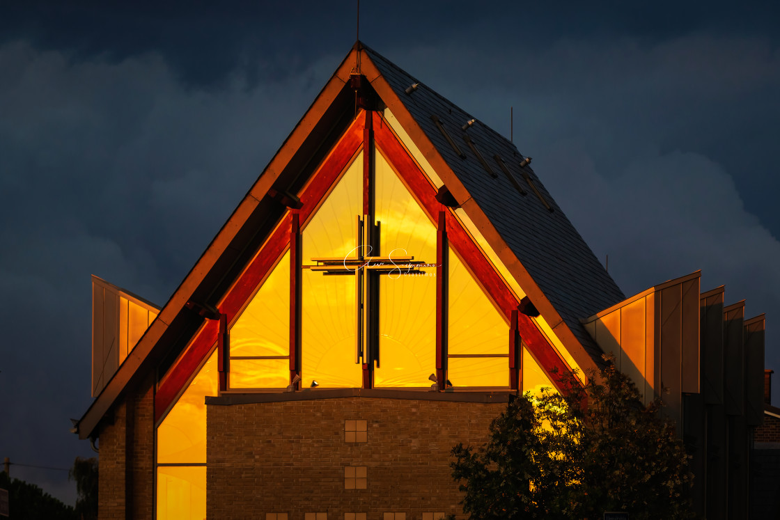 """Modern Church in golden light against a stormy evening sky."" stock image"