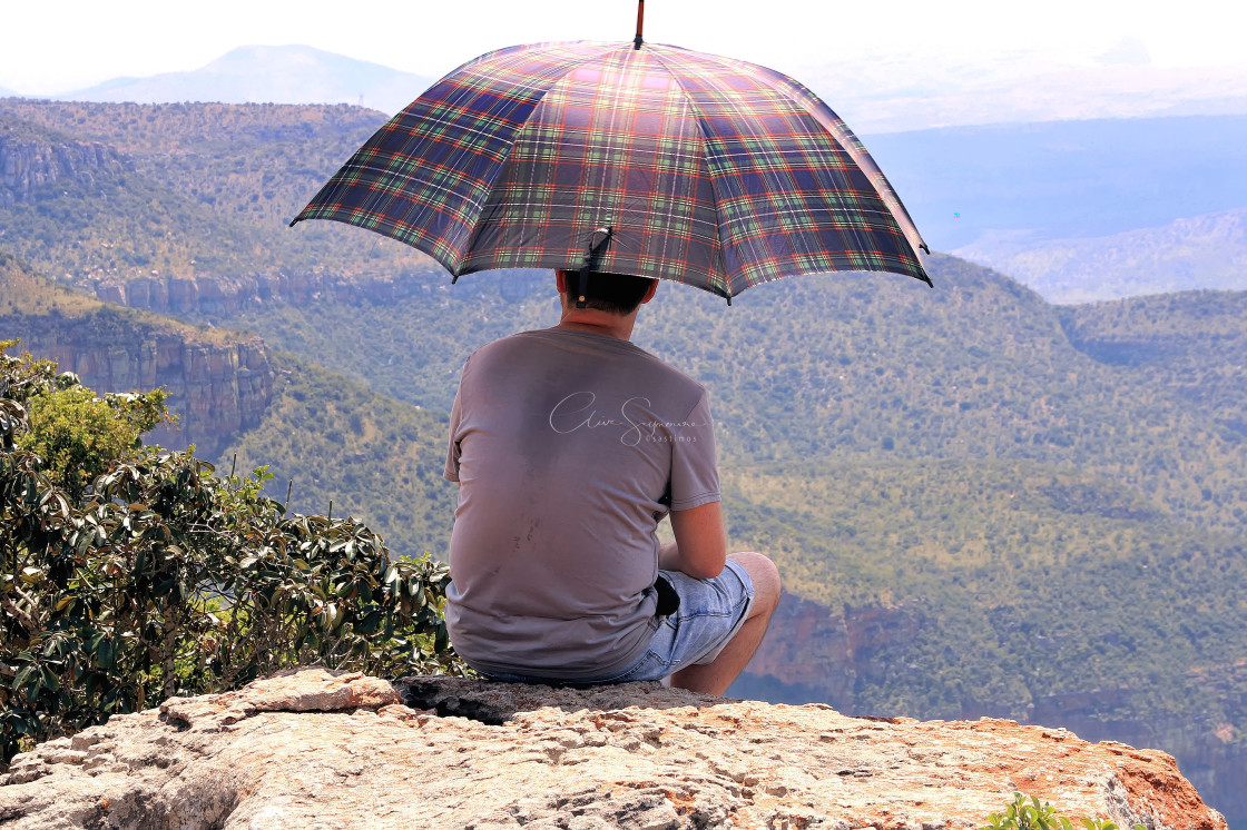 """""""Man sitting on a rock looking at a sweeping South African Vista."""" stock image"""