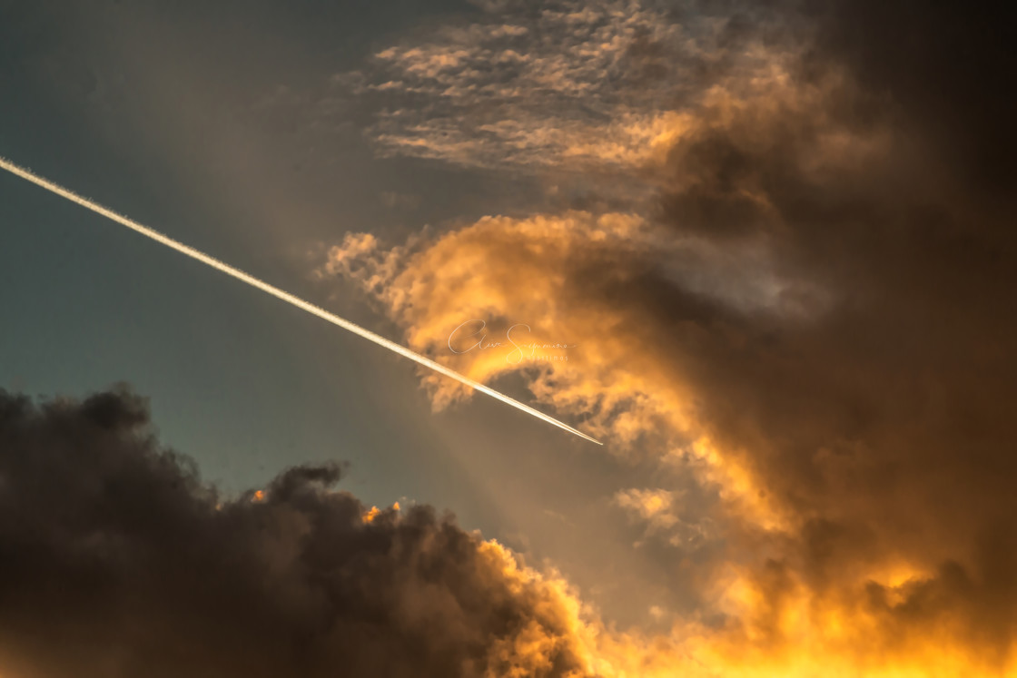 """""""Vapour trails in the sky at sunset."""" stock image"""