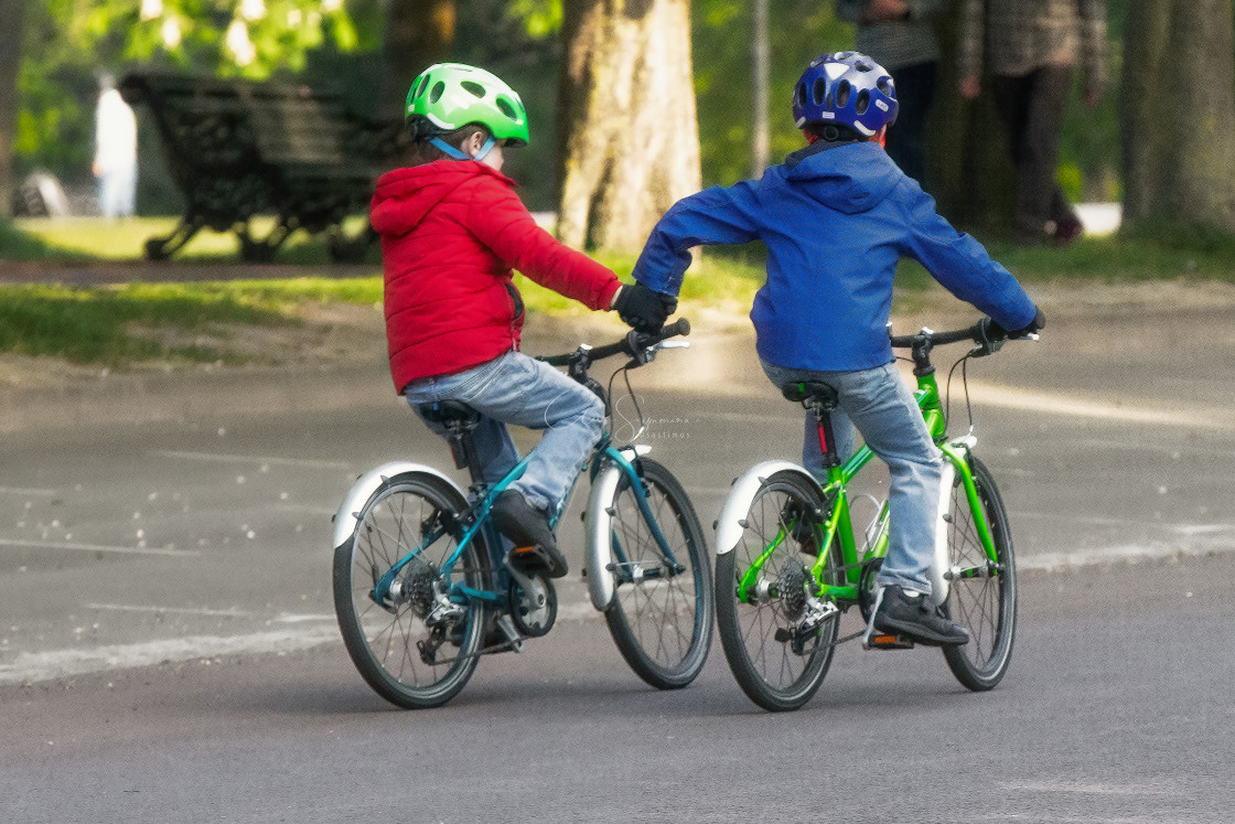 """Two boys on Bicycles, one giving the other a helping hand."" stock image"