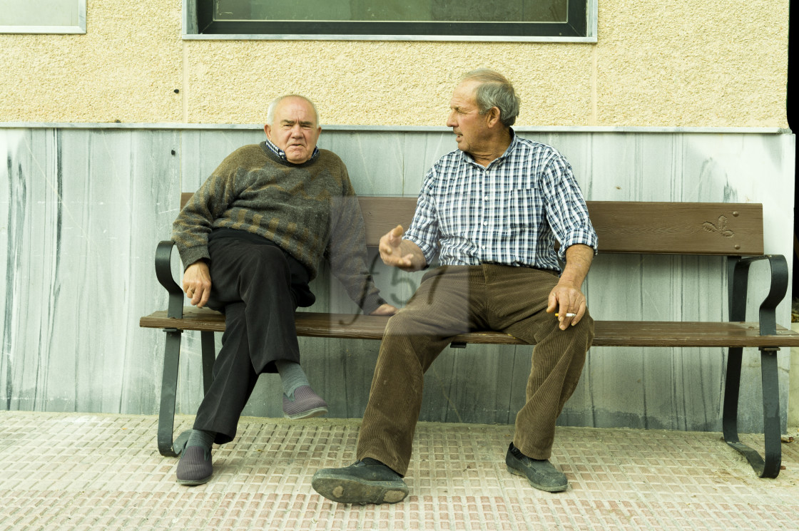 """""""Local men chat on a bench smoking a cigarette. Valle de Ricote, Murcia, Spain."""" stock image"""