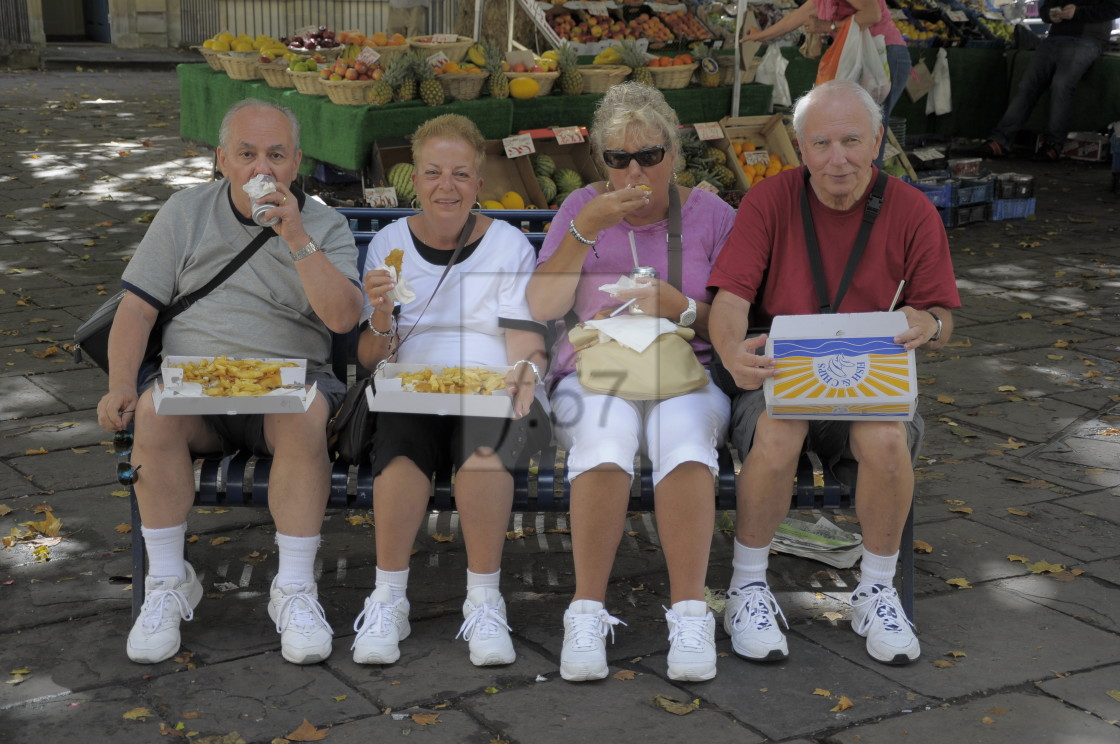 """""""American visitors to the UK enjoy a fish and chip lunch."""" stock image"""