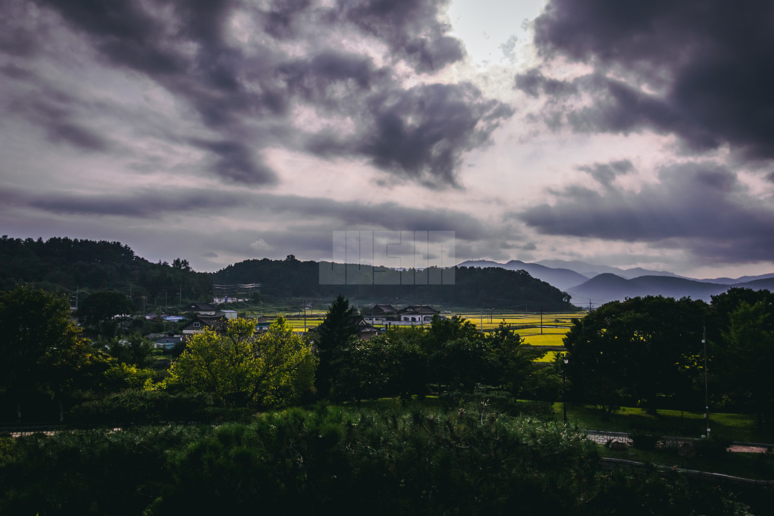 """Cloudy Sunset over the Korean Country Side"" stock image"