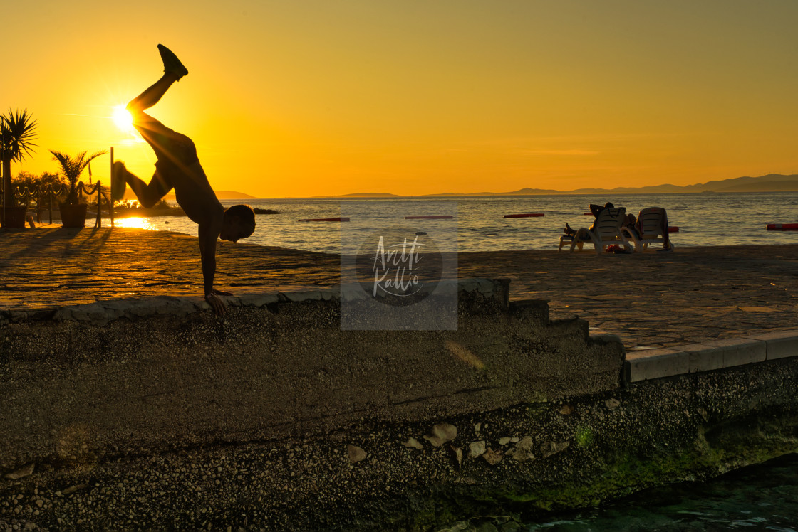 """Jump against the sunset"" stock image"