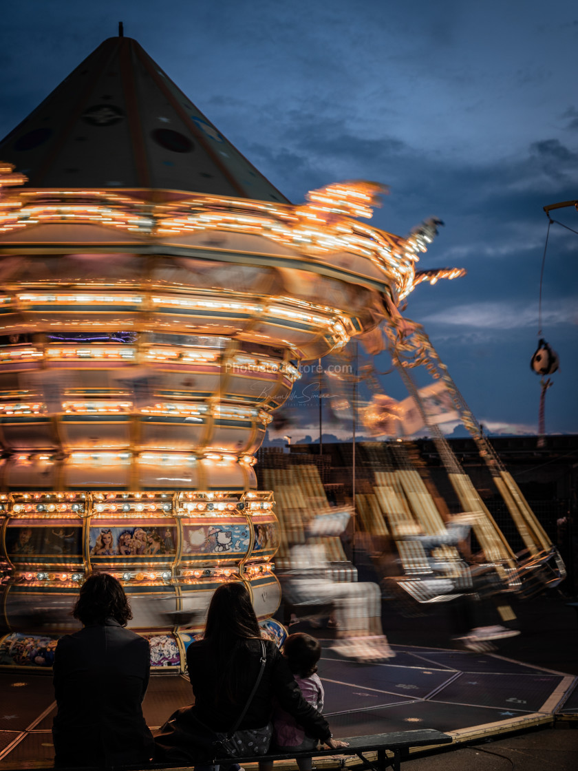"""""""Carousel with many lights turns fast in front of steady spectators, vertical..."""" stock image"""