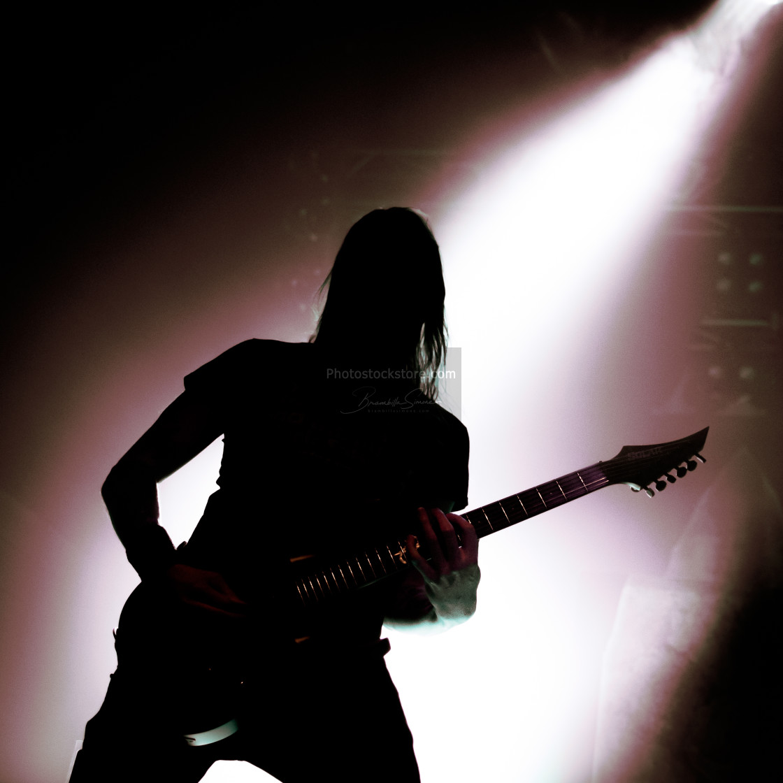 """silhouette of guitarist with falling light behind"" stock image"