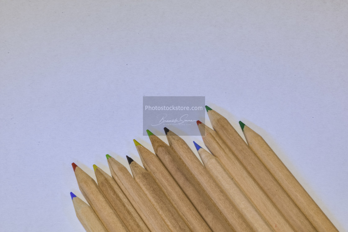 """colored crayons lined up on a white pape , horizontal image"" stock image"