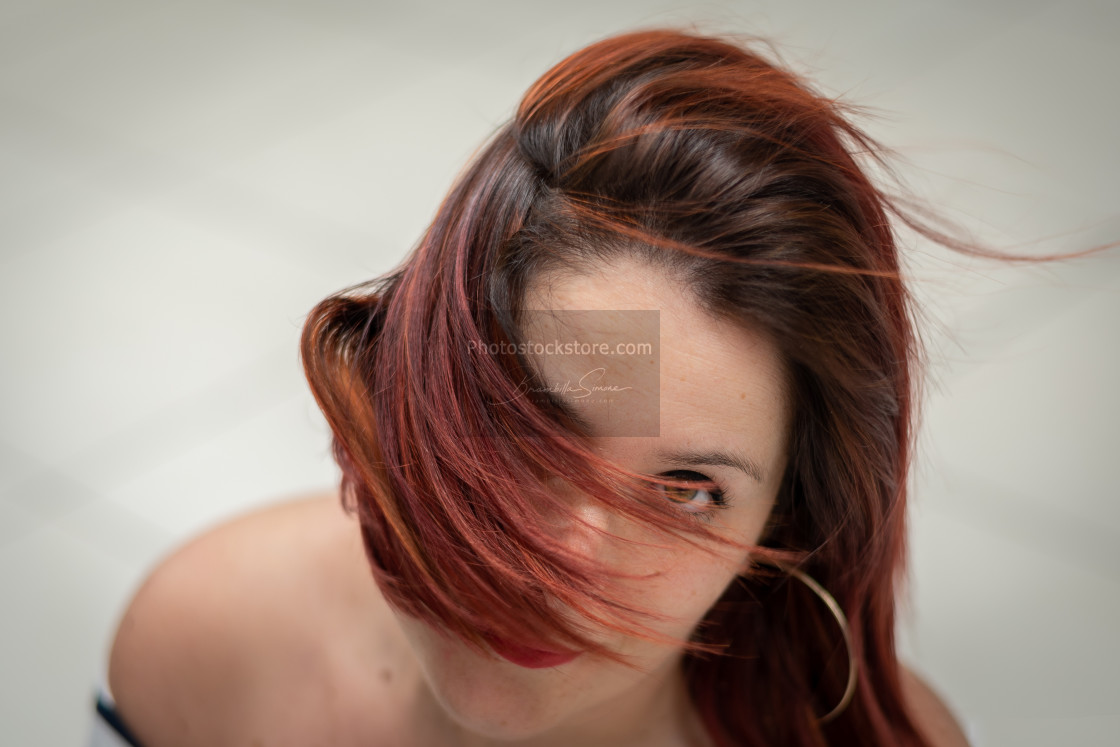 """Close-up portrait of Girl with wind-blown red hair in front of f"" stock image"