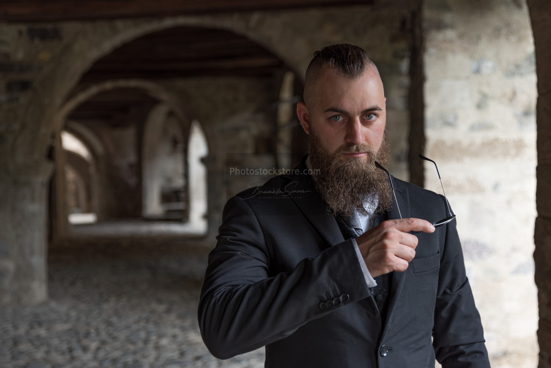 """Man with short hair and long beard holding sunglasses"" stock image"