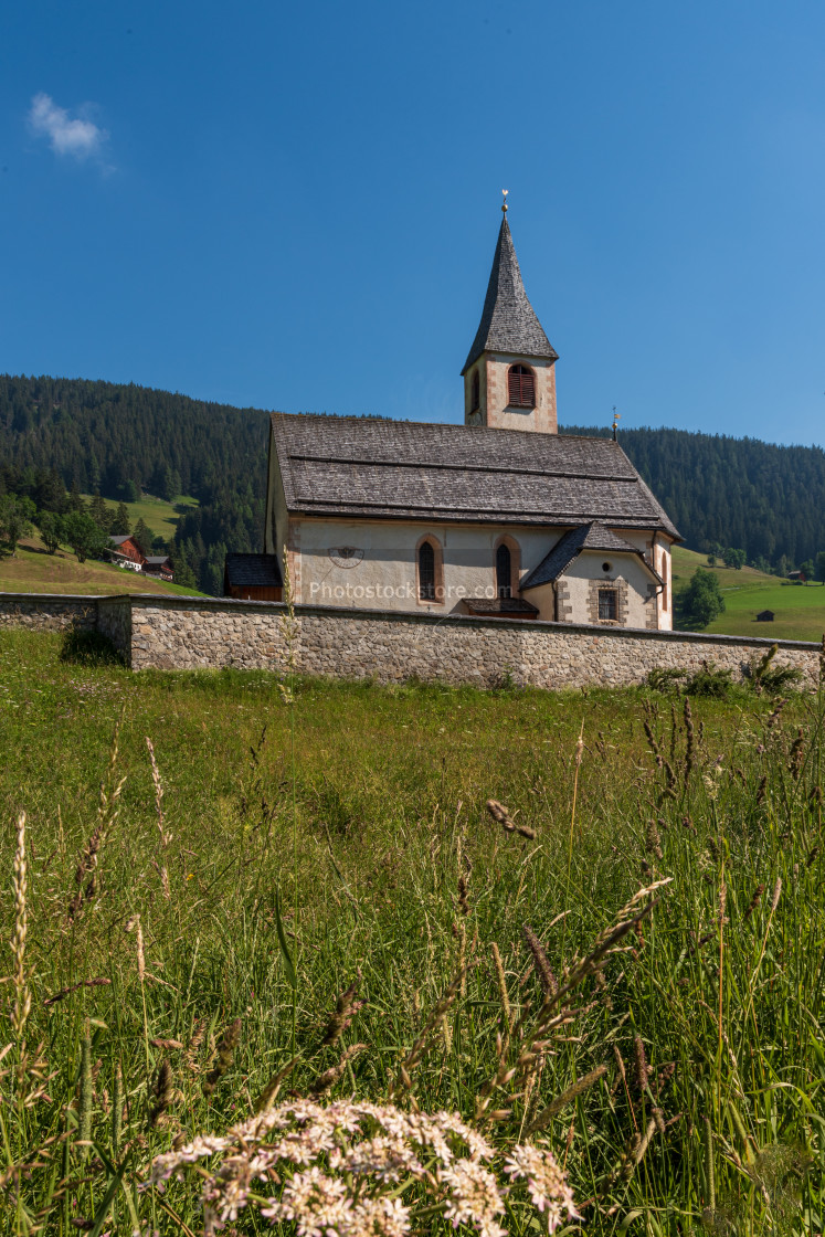 """""""South Tyrolean mountain church under a blue sky with a single wh"""" stock image"""