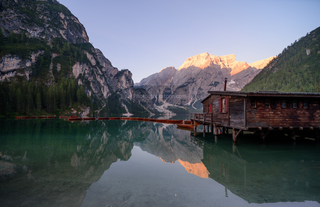 """""""The Seekofel mountains and wooden boats reflected in the waters"""" stock image"""