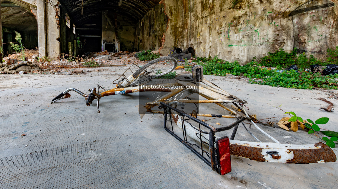 """Bicycle fallen to the ground in an abandoned and ruined place"" stock image"