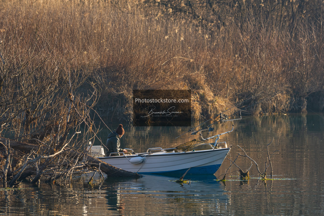 """""""Fisherman on a boat by the river in the early morning"""" stock image"""