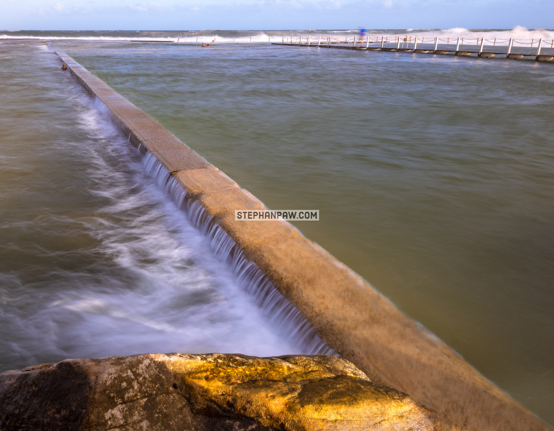"""Flow over the wall of North Narrabeen rock pool // Sydney, Austr"" stock image"