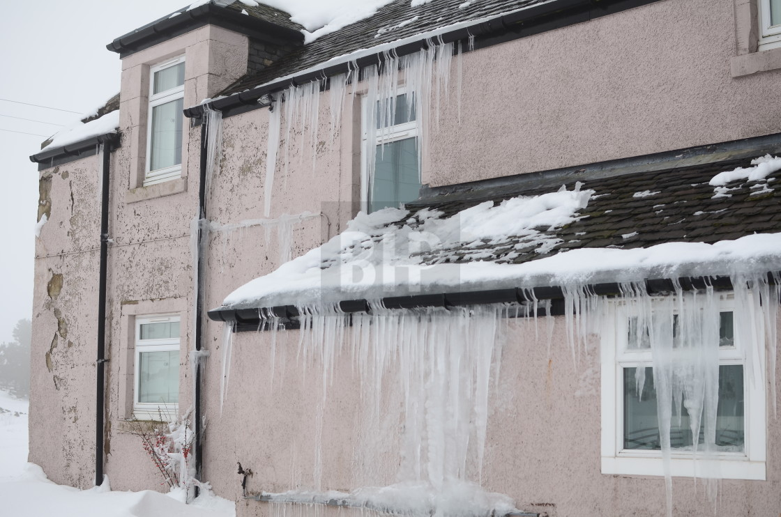 """Large Icicles on House Exterior"" stock image"