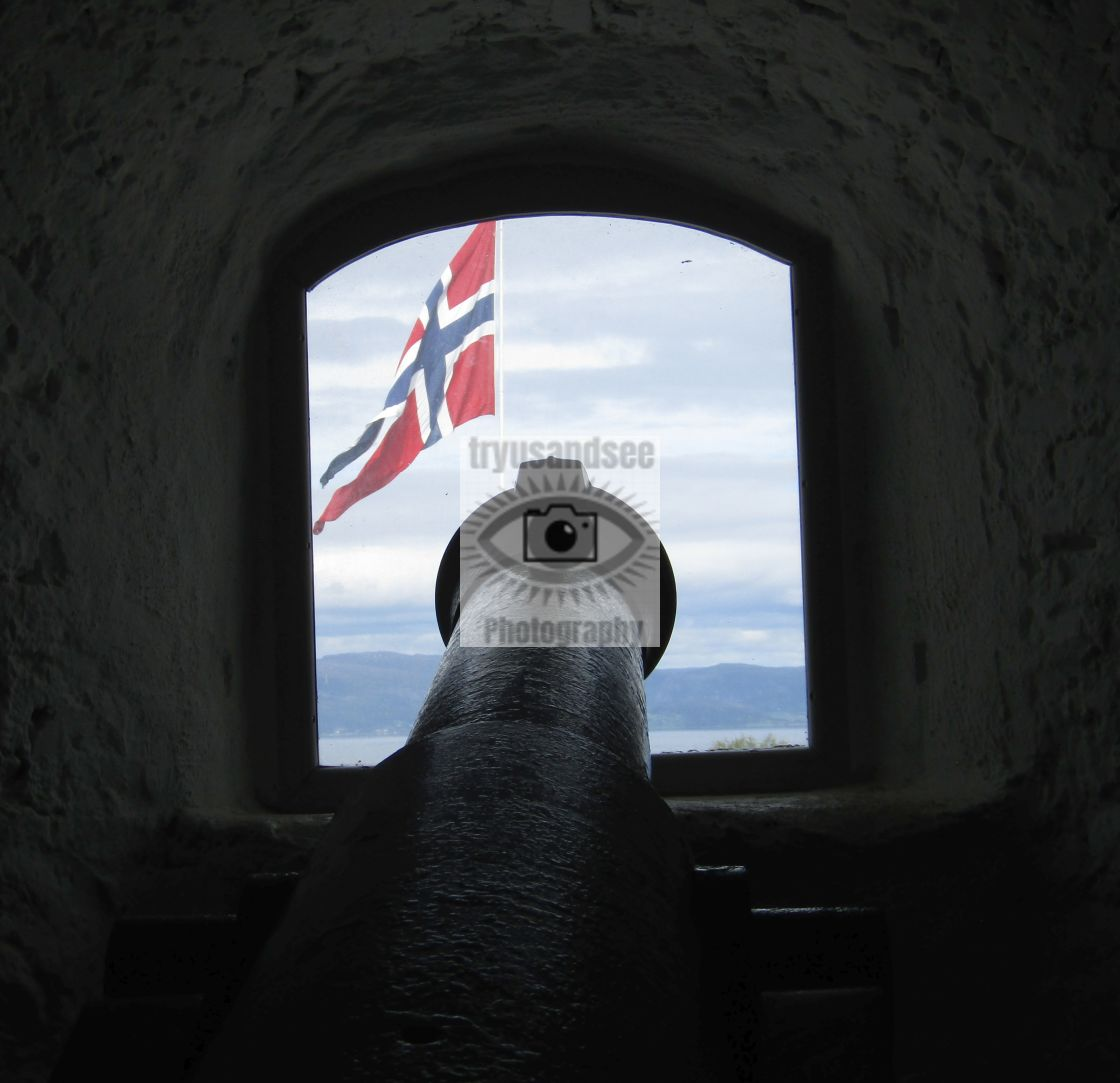 """Old cannon inside top of Kristiansen Fort overlooking flag"" stock image"