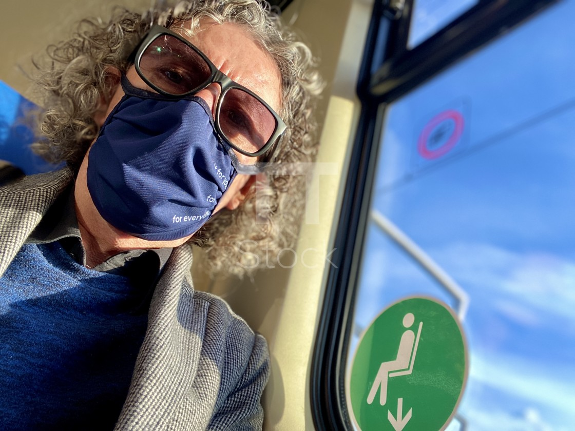 """Mature older man traveling on a commuter train during Corona epidemic wearing washable face mask."" stock image"