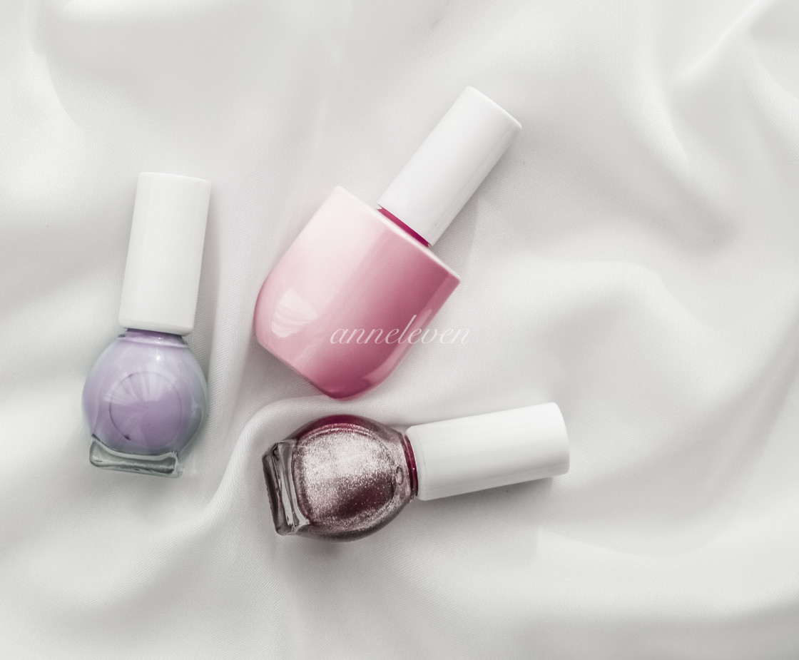 """Nail polish bottles on silk background, french manicure products and..."" stock image"