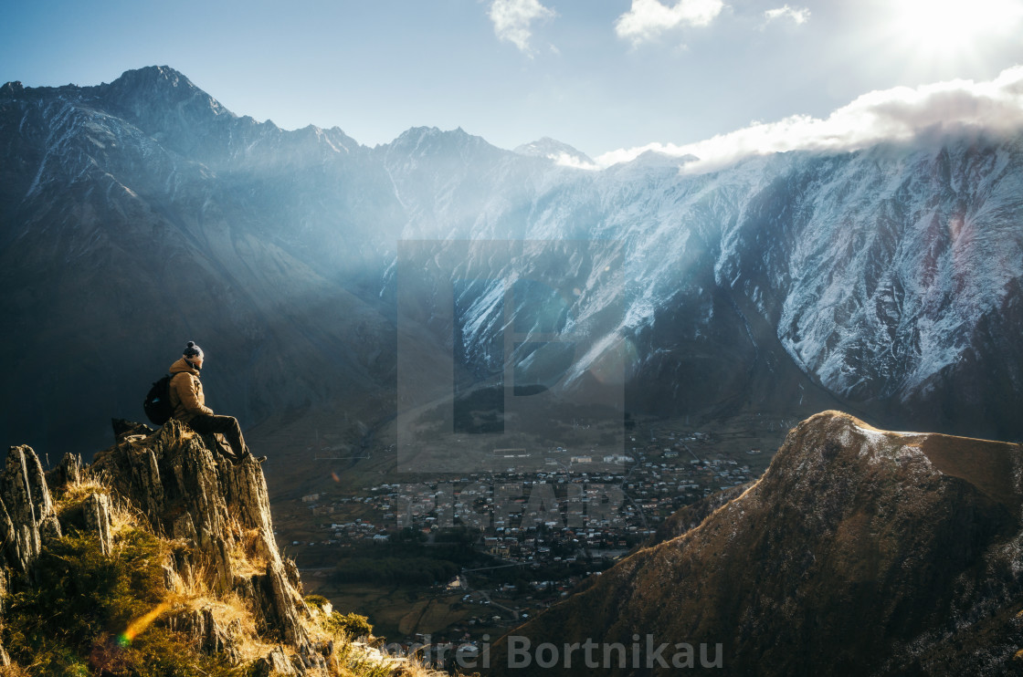 """Backpacker sit on cliff edge and looks at mount valley"" stock image"