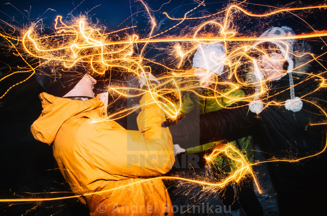 """Group of friends enjoying out with sparklers outdoors. Happy people celebrate christmas holidays"" stock image"