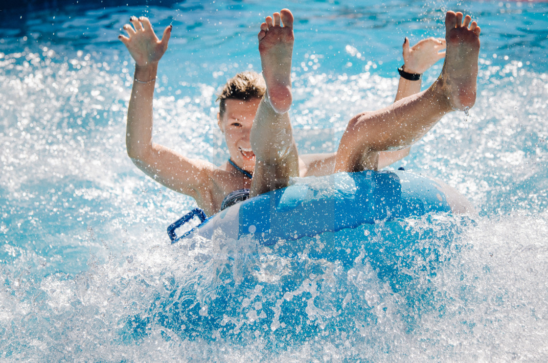 """""""Funny couple taking a fast water ride on a float splashing water. Summer vacation concept."""" stock image"""