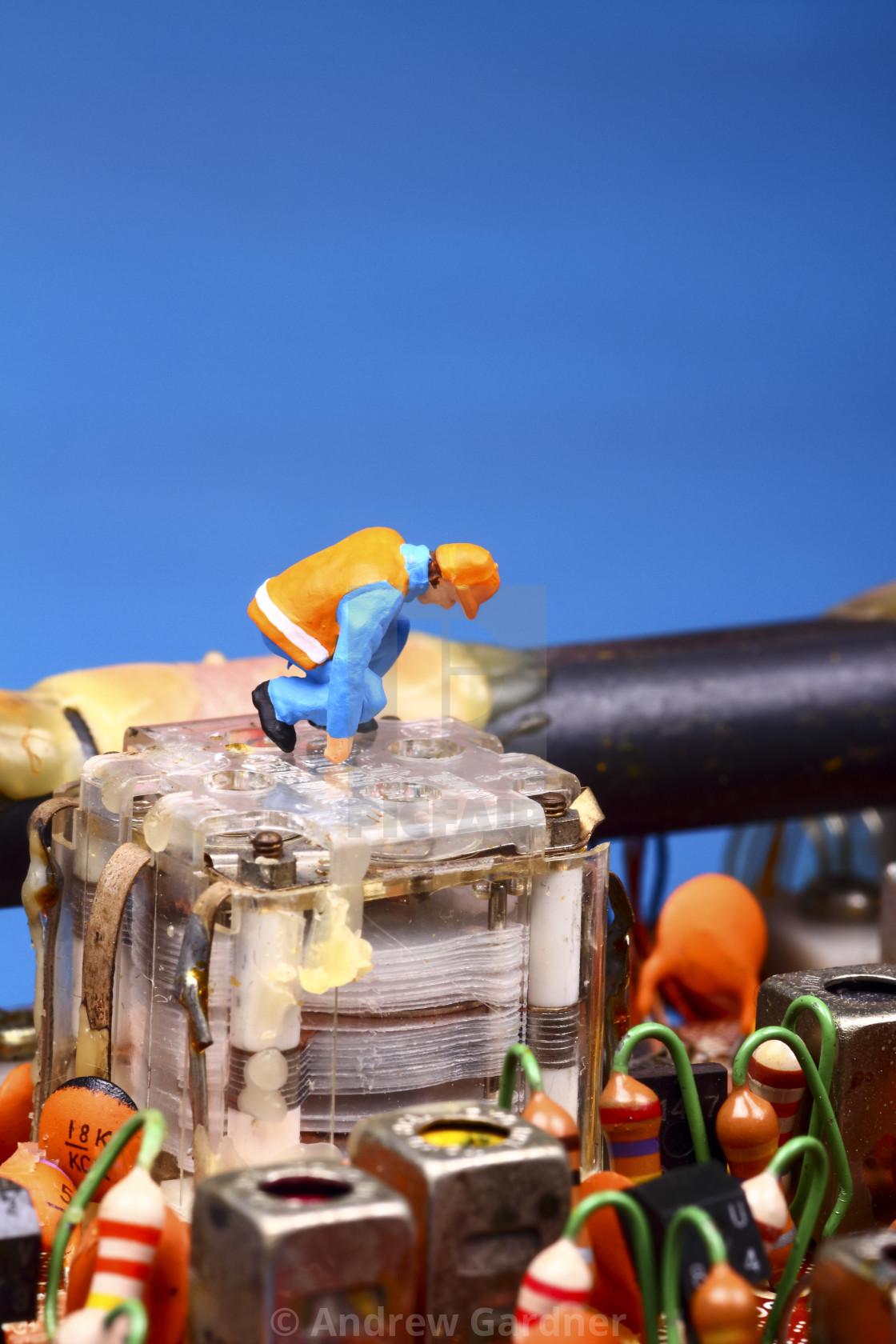 """Miniature figure workman inspecting a vintage radio circuit board radio repair concept"" stock image"