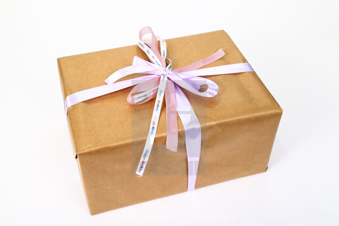 """Birthday gift wrapped in simple brown paper with ribbon tied in a bow"" stock image"