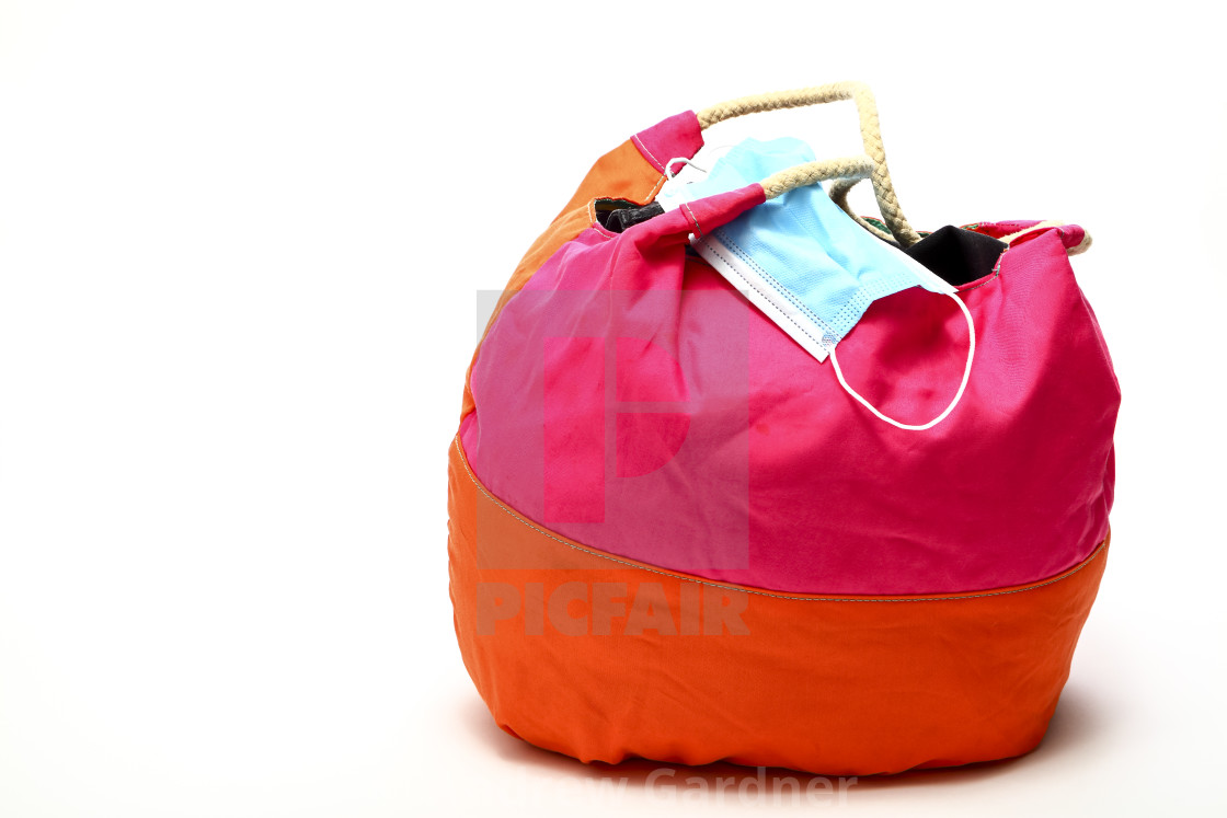 """""""Brightly coloured round carryall with a medical face mask travel in a covid environment concept"""" stock image"""