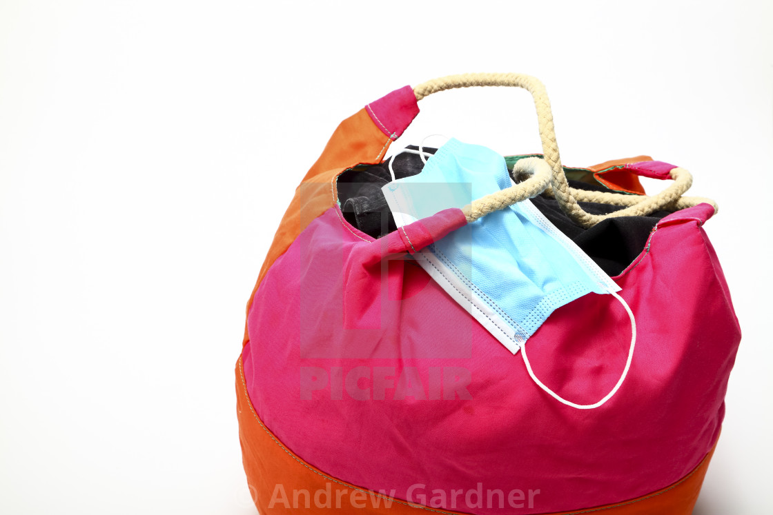 """Brightly coloured round carryall with a medical face mask travel in a covid environment concept"" stock image"