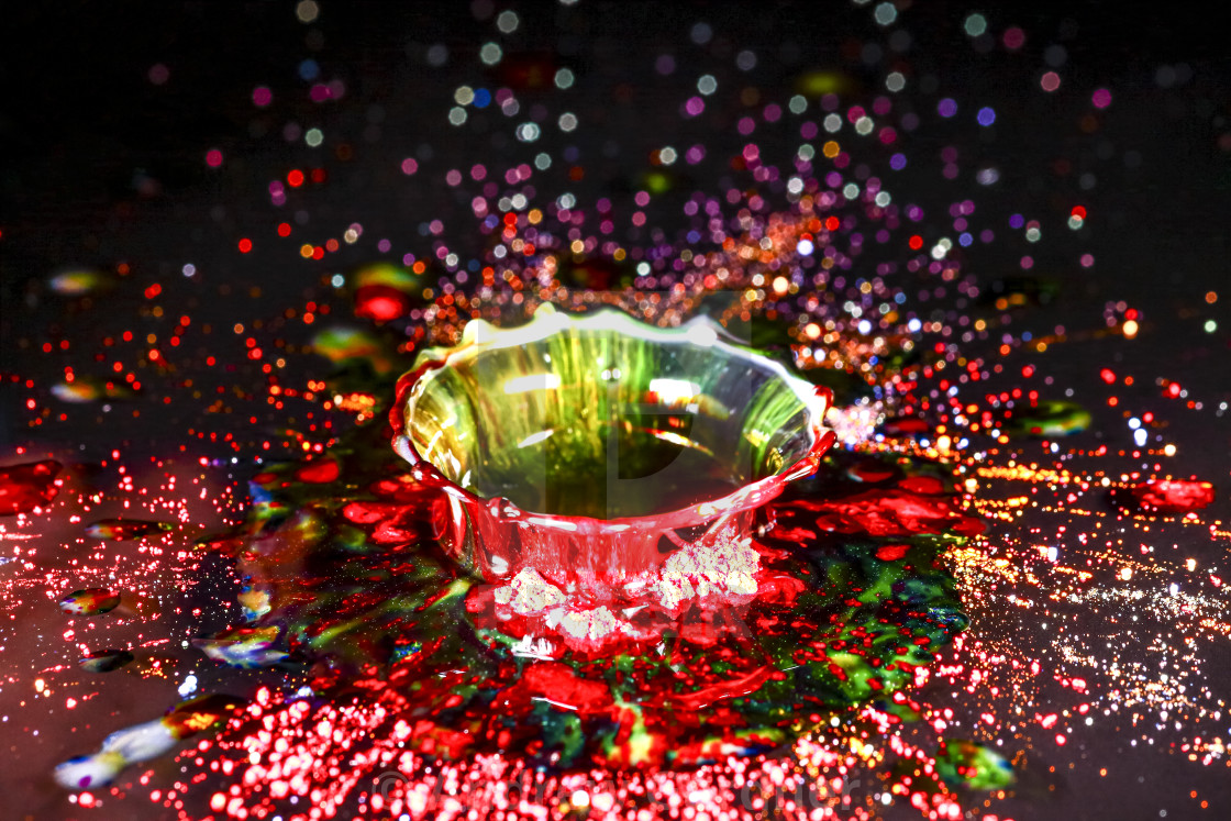 """Drops of water colliding with powdered dye to create a multi coloured abstract droplet collision"" stock image"