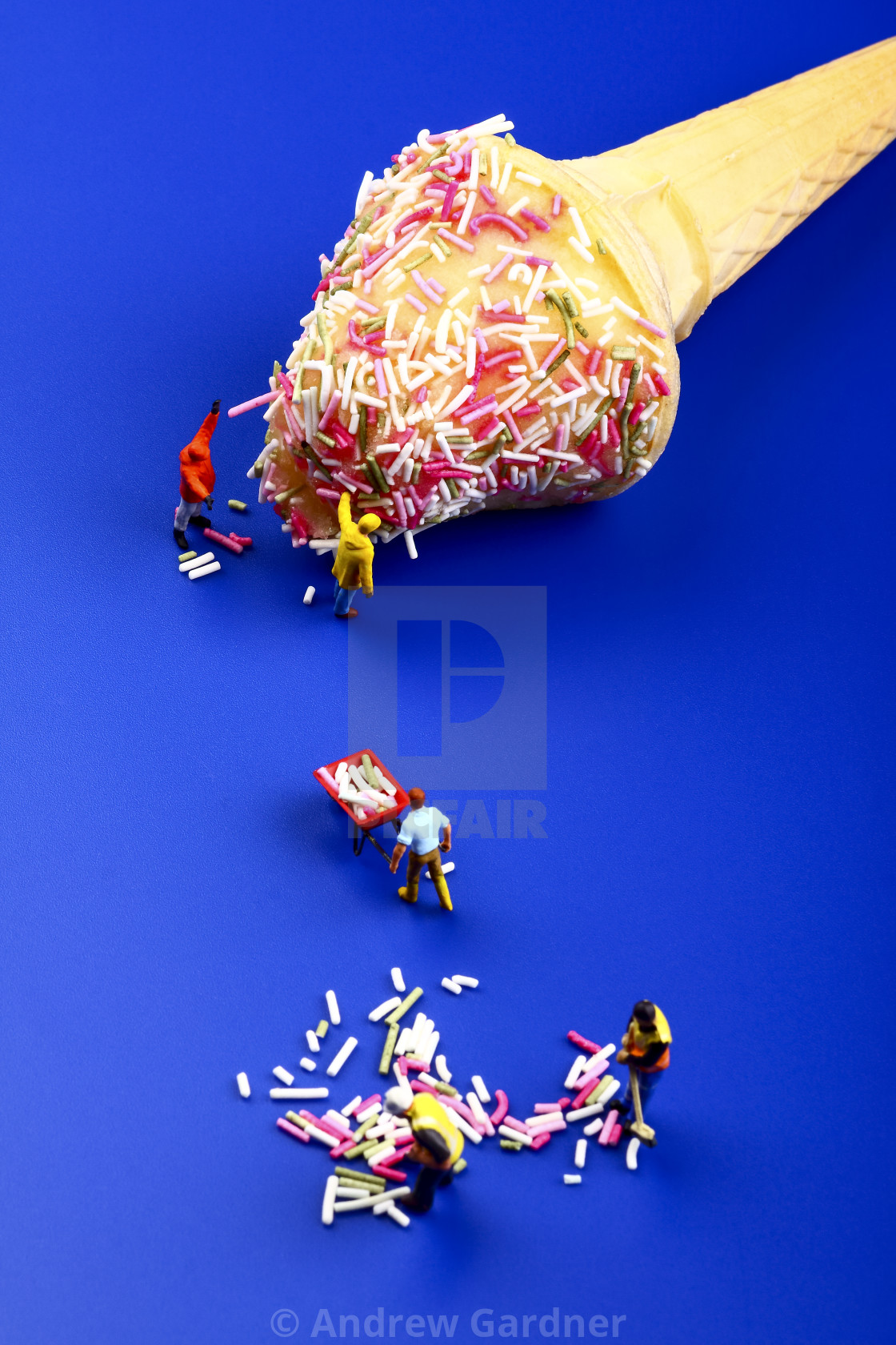 """Miniature figure people topping an ice cream cone with hundreds and thousands"" stock image"