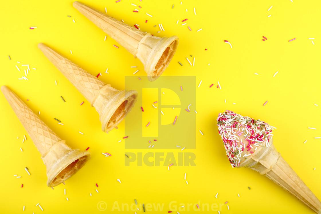 """Ice cream cones with hundreds and thousands on a bright yellow background"" stock image"