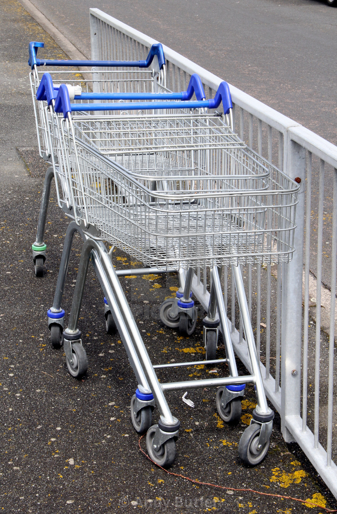 """""""Shopping Carts abandoned at side of road next to metal fence."""" stock image"""
