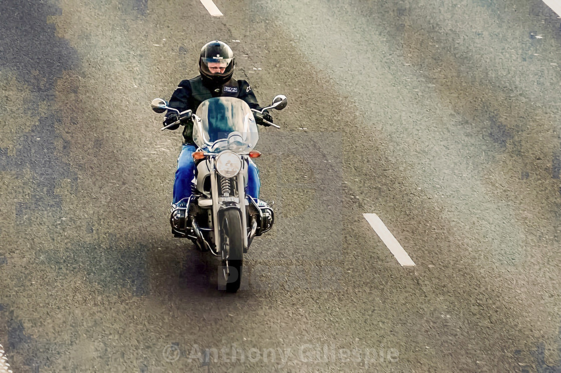 """""""A Lone Biker on a Tar Road"""" stock image"""
